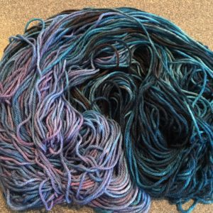 An overdyed skein of yarn with dark and light blue tones and sections of violet.