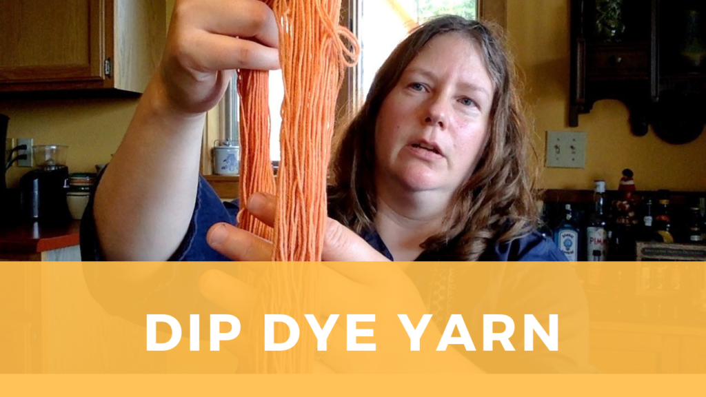 Sarah shows off a skein of dip dyed yarn that is coral and peach colored