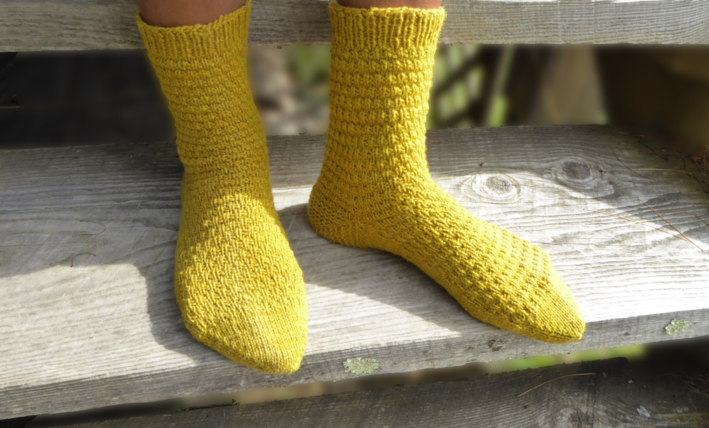Bethel socks modeled on feet. The nubbly texture is set off beautifully on yellow yarn.